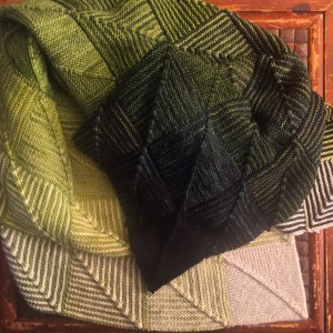 My greens and creams Hue Shift blanket in a pile on my coffee table.